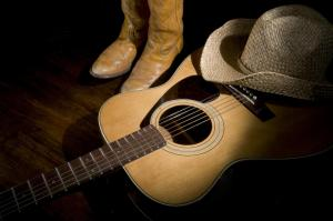 all about country music - spotlight on guitar, cowboy boots and cowboy hat