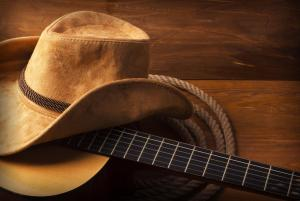 top country shows - cowboy hat and rope next to guitar