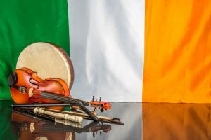 musical instruments on black table in front of Ireland's flag